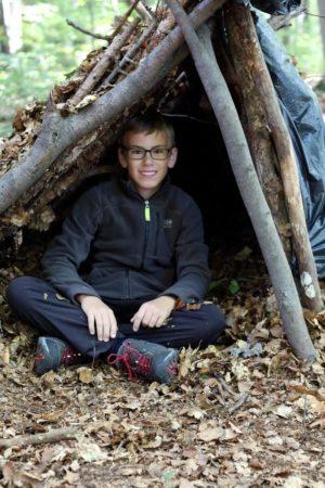 Kinder Survival Kurs: Junge sitzt in selbst gebauter Behausung